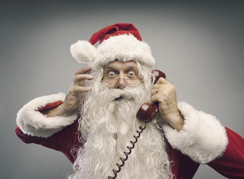 Stressed Santa Claus on the phone. Stressed panicked Santa Claus answering phone calls on Christmas eve, he is staring at camera with eyes wide open royalty free stock photos
