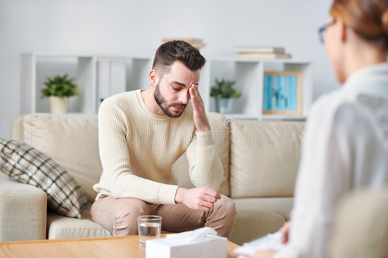 Stressed patient. Stressed young men touching forehead while sitting on couch and sharing his problems with counselor royalty free stock photos