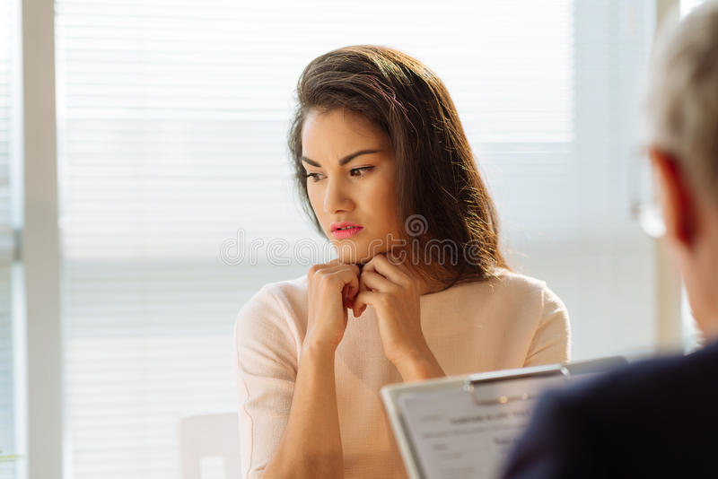 Stressed pensive young woman. Stressed pensive young women at the consultation with psychiatrist stock image