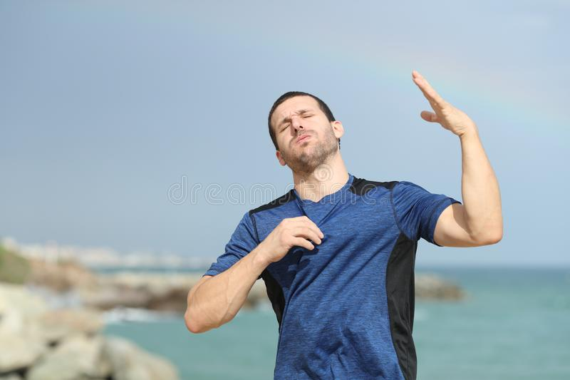 Stressed runner suffering heat stroke on the beach. Stressed runner suffering heat stroke complaining and fanning with his hand on the beach stock image