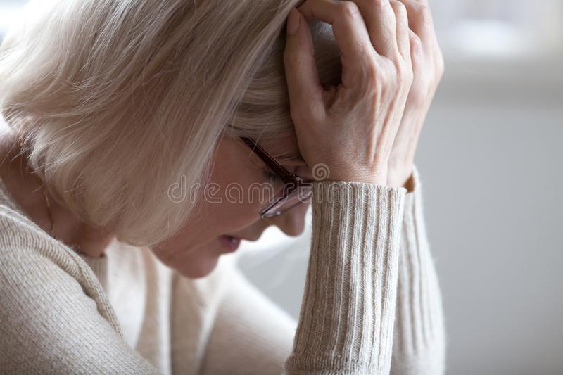 Sad tired senior woman holding head in hands feeling headache stock images