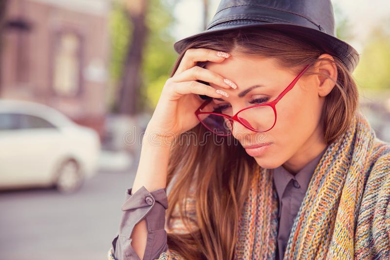 Stressed sad woman sitting outdoors. City urban life style stress stock photos