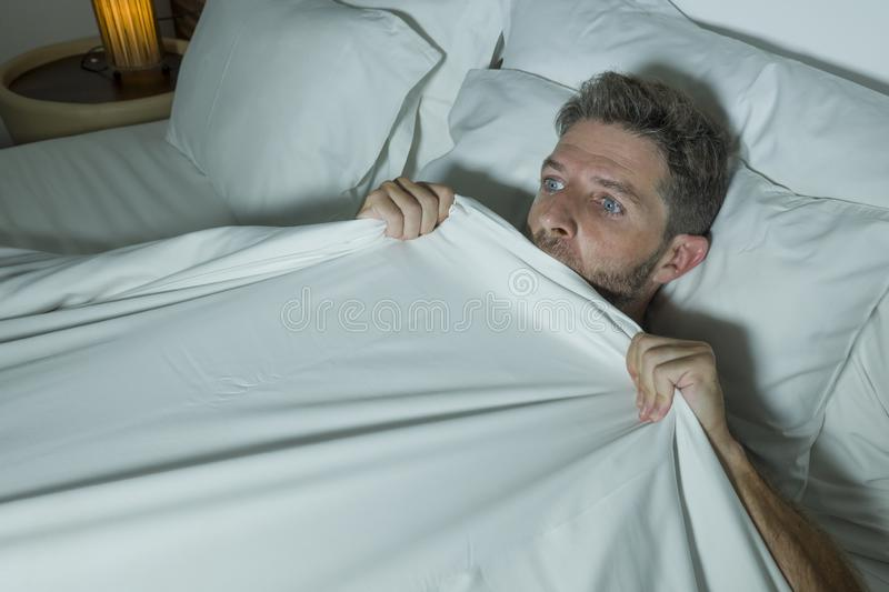 Stressed and scared man alone in bed awake at night in fear after having a nightmare feeling paranoid holding the blanket in royalty free stock image