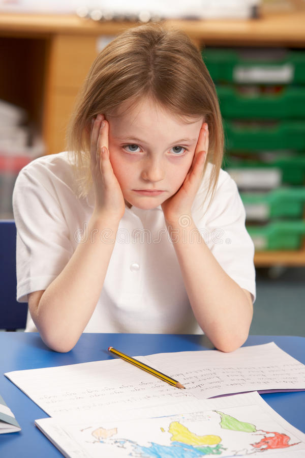Stressed Schoolgirl Studying In Classroom stock photos