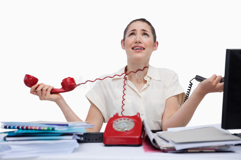 Stressed secretary answering the phones stock photography