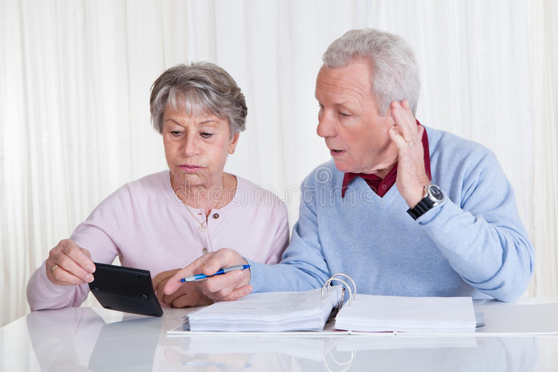 Stressed senior couple calculating budget royalty free stock photography