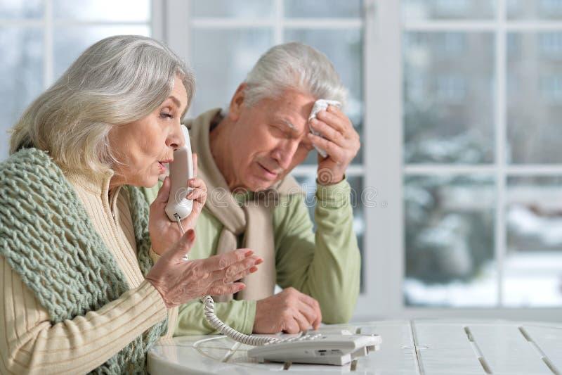Stressed senior couple. Talking on the phone stock image
