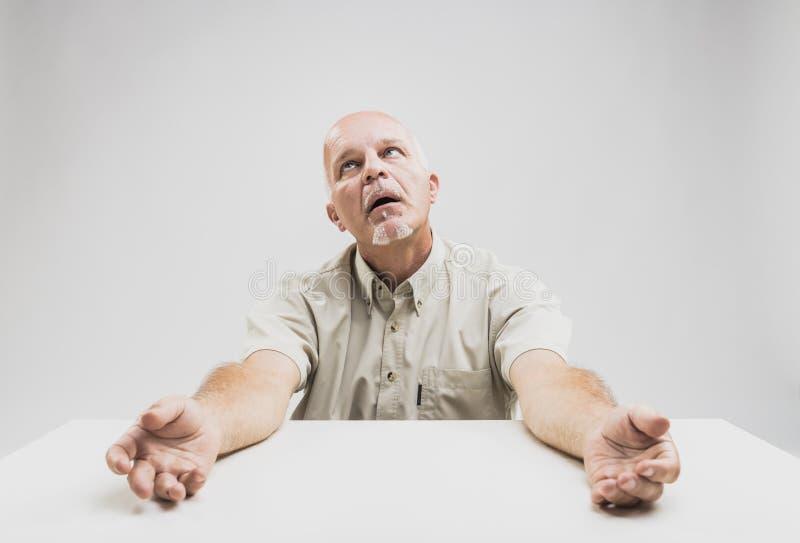 Stressed senior man looking up imploringly royalty free stock photo