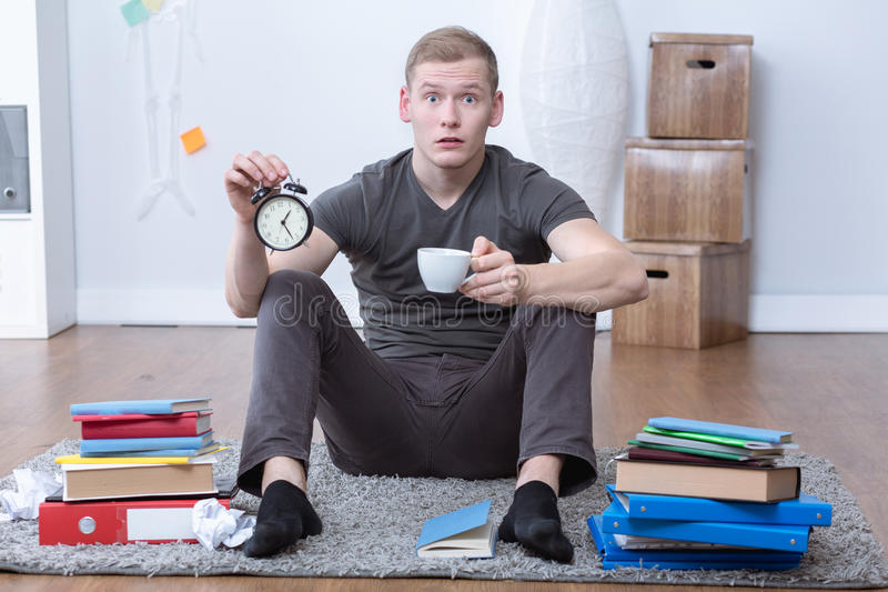 Stressed student holding alarm clock royalty free stock photography