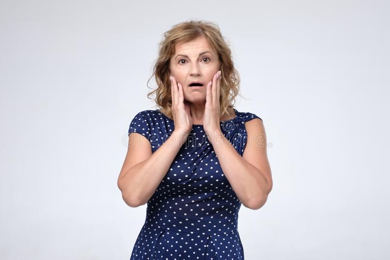 Stressed surprised mature woman looking at camera worried about facial wrinkles royalty free stock photos
