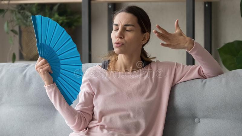 Stressed sweaty woman waving fan suffer from heat at home. Stressed sweaty young woman holding waving fan suffer complain on heat at home, overheated annoyed stock image