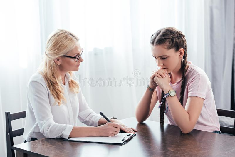 Stressed teenage girl sitting at table on therapy session by female counselor writing in clipboard. In office stock photos