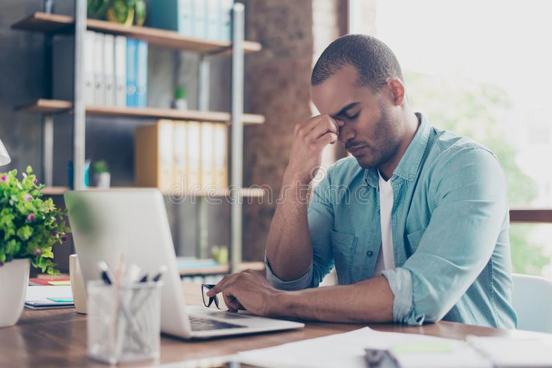 Stressed tired mulatto freelancer is having headache and thinking how to finish his work. He is in a casual smart, sitting and royalty free stock images