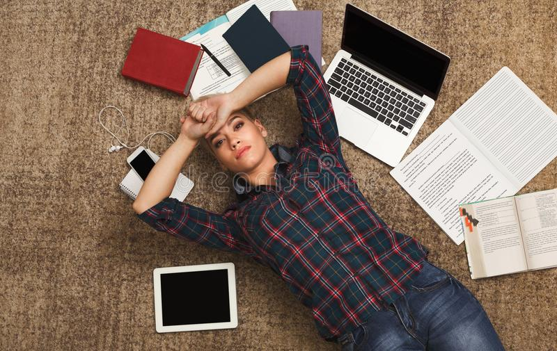 Tired student girl lying on the floor with books and gadgets stock photography