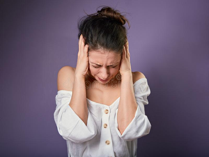 Stressed unhappy casual woman closed ears the fingers because not want the hear any sounds and noise on purple background. Closeup stock images