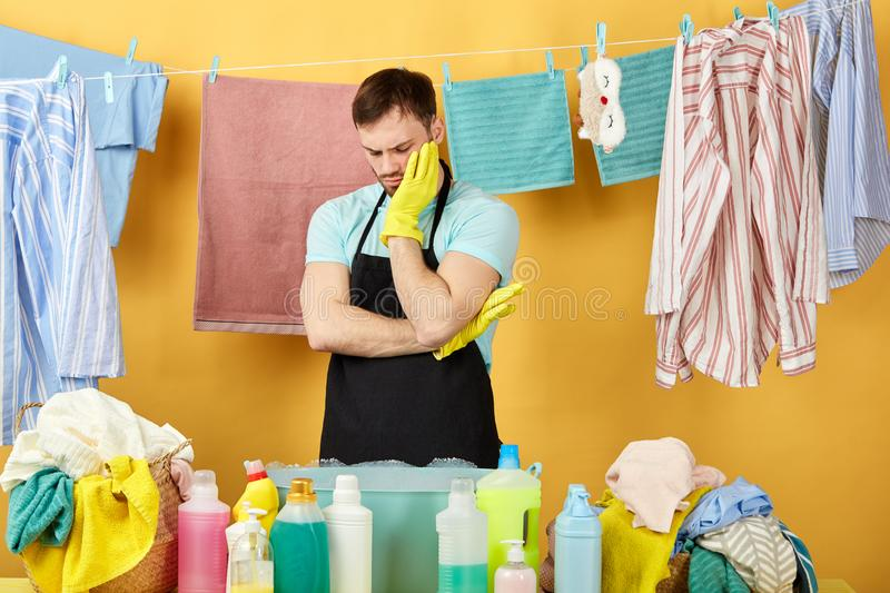 Stressed unhappy man with hand on his cheek having a rest while doing housework, royalty free stock image