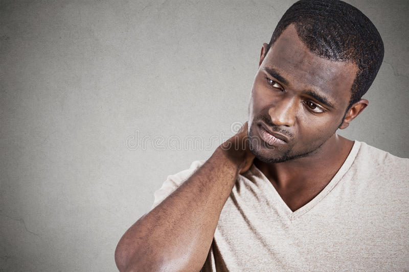 Stressed, unhappy young handsome man with neck pain stock photography