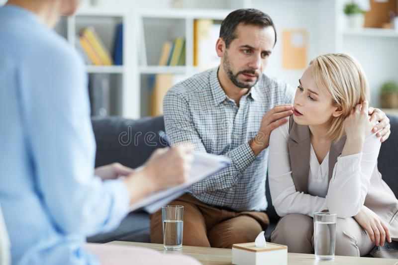 Stressed wife. Tired blonde female sitting in front of counselor and describing her opinion about reasons for permanent stress royalty free stock photos