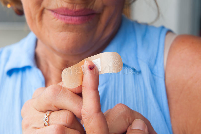 Stressed Woman band aid bloody finger wound. Portrait stressed woman in pain, suffering, close up of band aid on injured, cut bloody finger wound stock photography