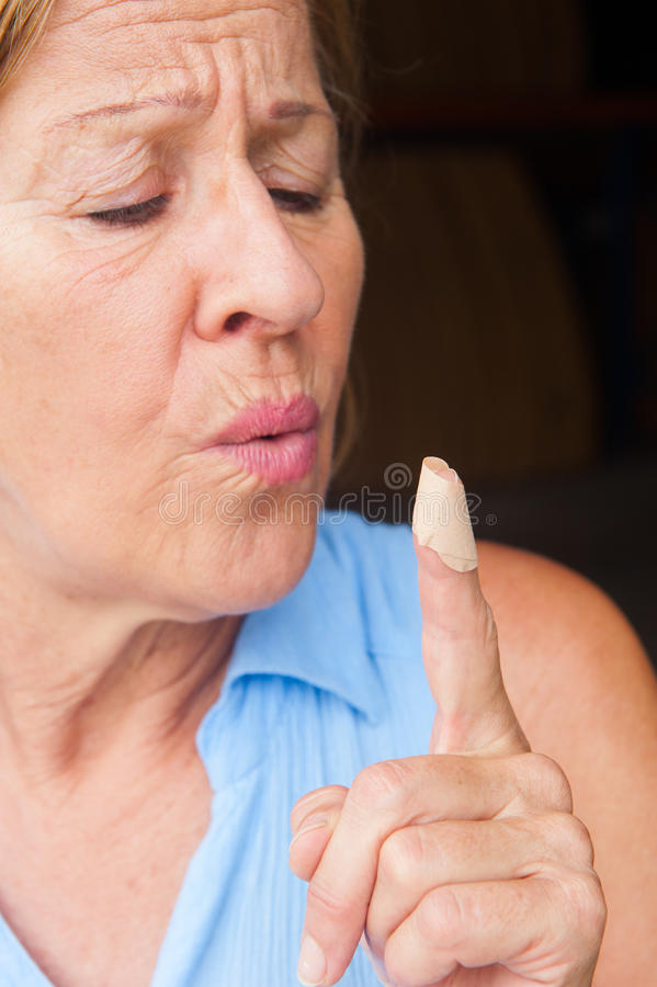 Stressed Woman blowing band aid finger wound. Portrait mature woman in pain, hurt and suffering, close up of band aid on injured finger wound stock images