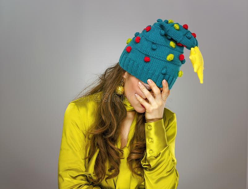 Stressed woman in Christmas hat isolated on grey background royalty free stock images