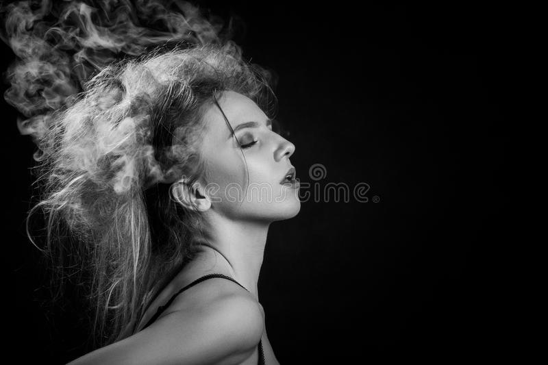 Smoke on head. Stressed woman with cloud of smoke on her head on black background, monochrome stock image
