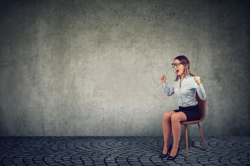 Stressed woman company employee sitting on a chair screaming in desperation. Stressed frustrated woman company employee sitting on a chair screaming in royalty free stock photo