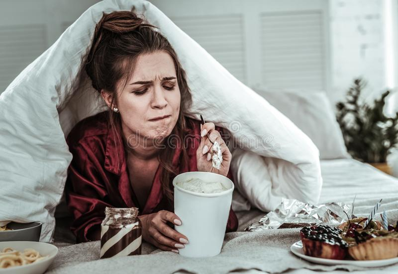 Stressed woman covered with a blanket eating sweets stock photography