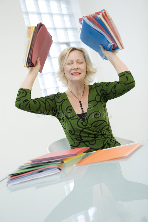 Stressed woman with folders. Mature woman in a workplace holding up several multicolored folders. Photo from Shoot with Ron contest royalty free stock images