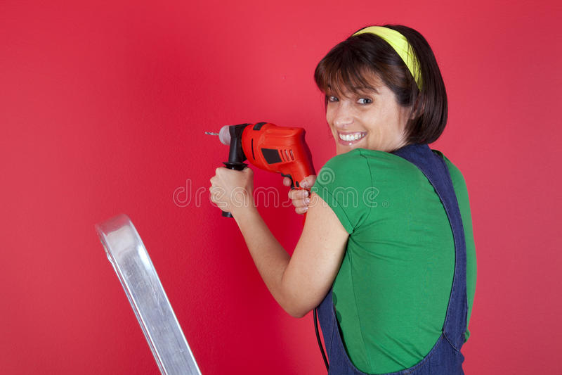 Stressed woman holding a electric drill royalty free stock images