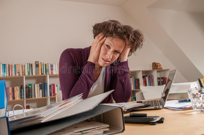 Stressed woman in the office stock image