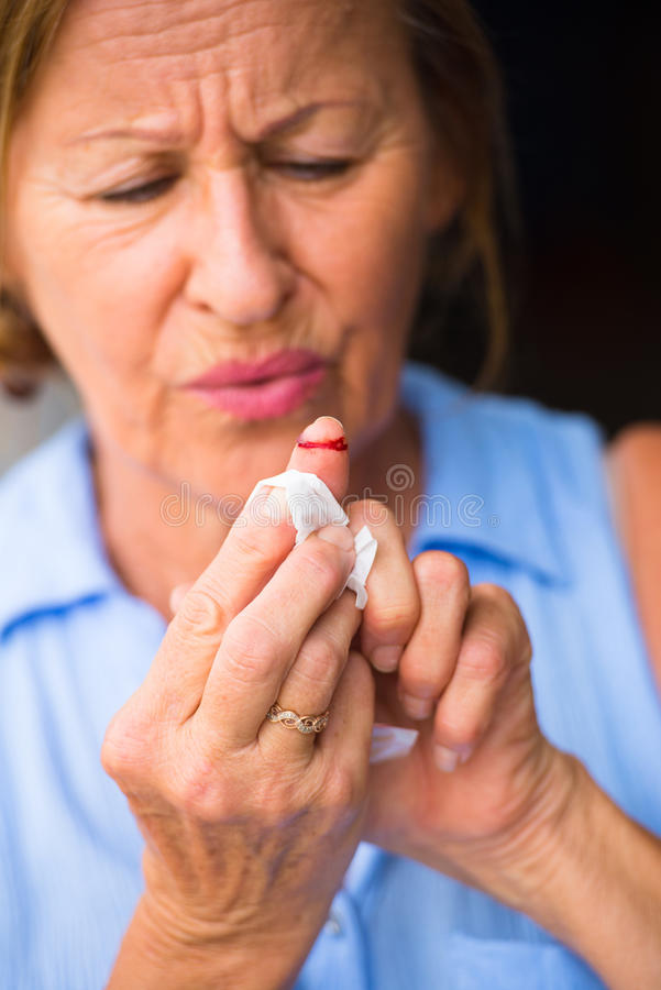 Stressed Woman painful bloody finger wound. Portrait stressed senior woman in pain, suffering, close up of tissue on injured, cut bloody finger wound royalty free stock photo