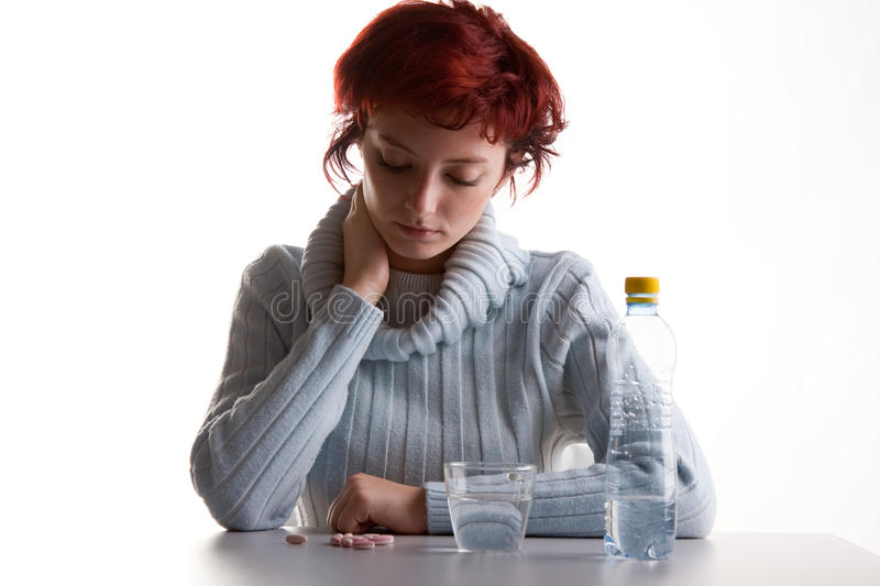 Stressed woman with pills. Half body portrait of stressed young woman sat at table with bottle of water and pills, isolated on white background royalty free stock photography