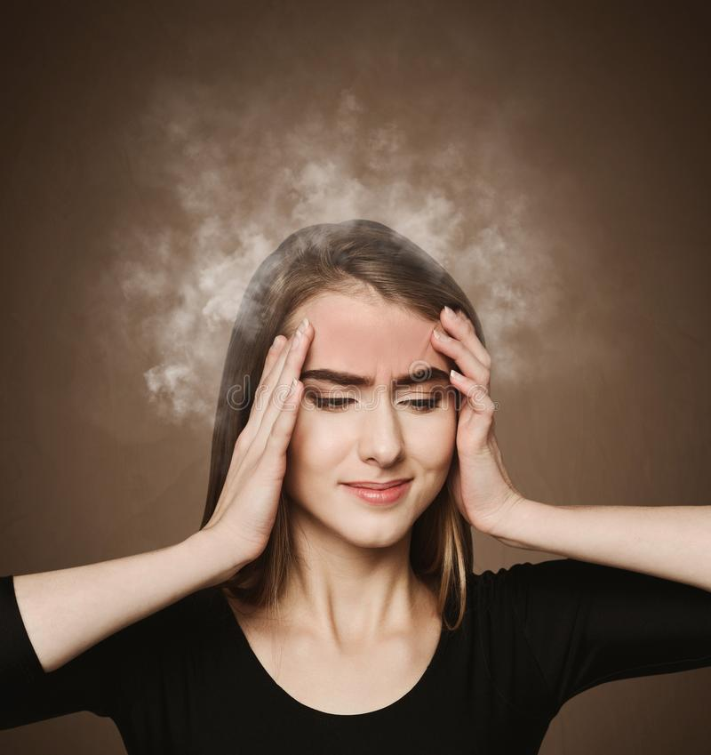 Exhausted girl with exploding head. Stressed woman with smoking head at dark background royalty free stock image
