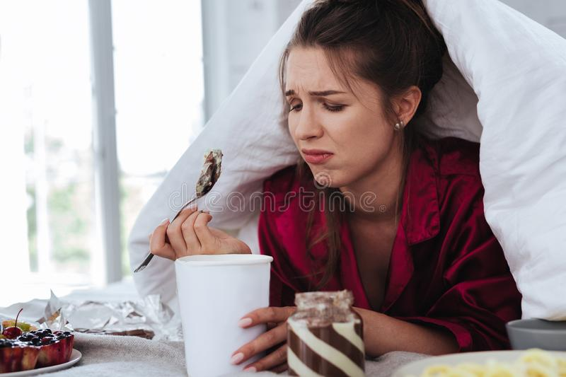 Stressed woman hiding under coverlet eating ice cream. Stressed woman. Stressed crying woman hiding under coverlet while eating ice cream and other desserts stock photos
