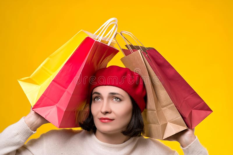 Stressed woman tired of shopping. Young woman in beret among shopping bags. Seasonal sales, shopping concept. Woman after shopping. Christmas holiday stress royalty free stock photos
