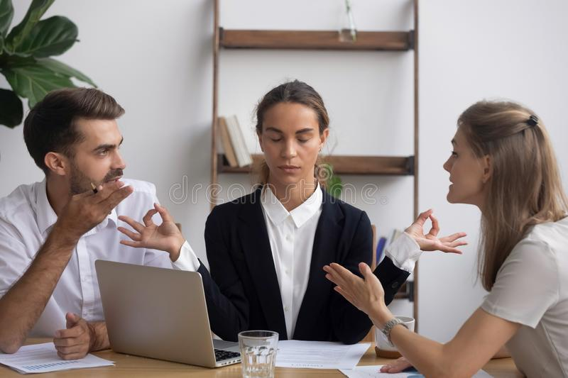 Stressed worker meditating at workplace ignoring arguing colleagues at meeting royalty free stock photo