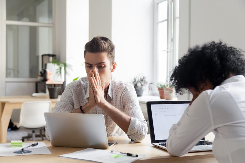 Stressed workers reading company bankruptcy news online. Upset millennial workers feeling despair witnessing company crisis online, stressed colleagues royalty free stock photos