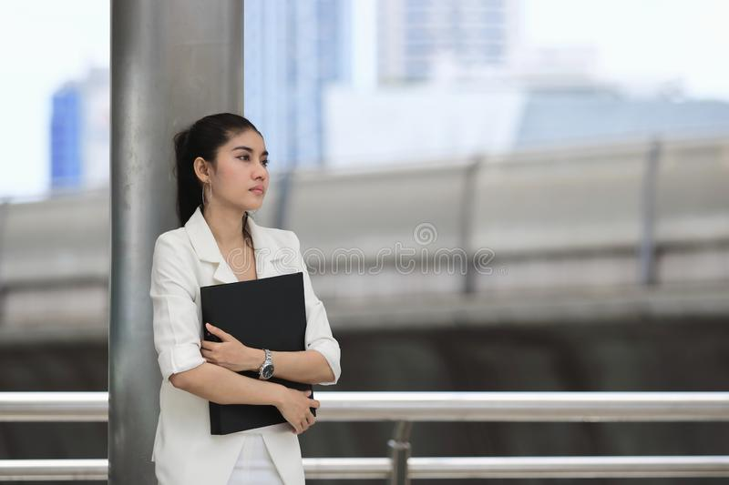 Stressed young Asian business woman with document folder standing at outside office royalty free stock photos