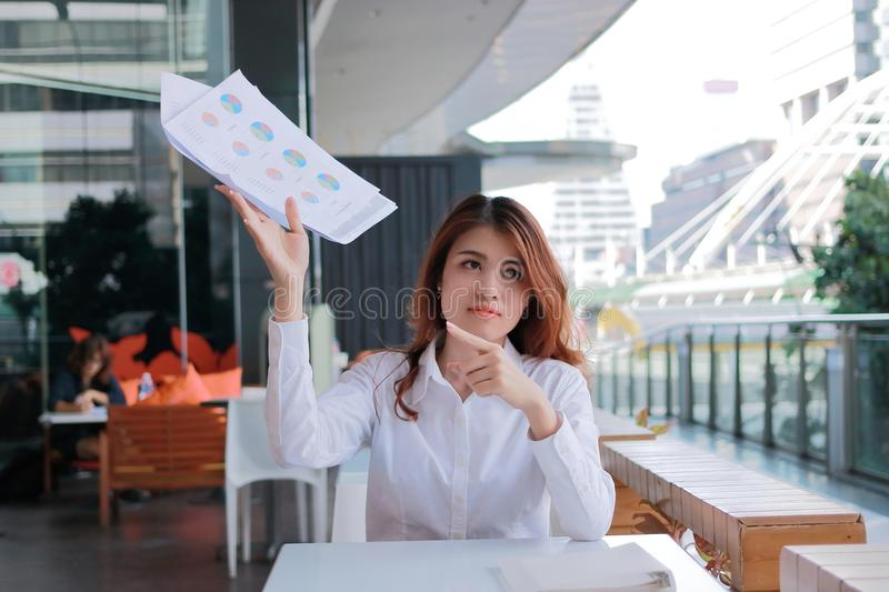 Stressed young Asian business woman pointing charts or paperwork at office. stock photos