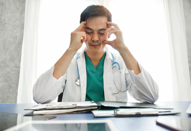 Stressed Young Asian male doctor is working. stock photography