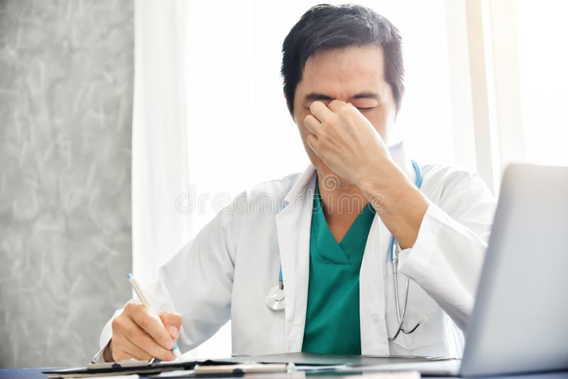 Stressed Young Asian male doctor is working. stock photo
