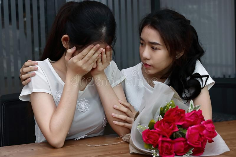 Stressed young Asian woman supporting depressed crying female friend in living room. Break up or best relationship concept. royalty free stock image