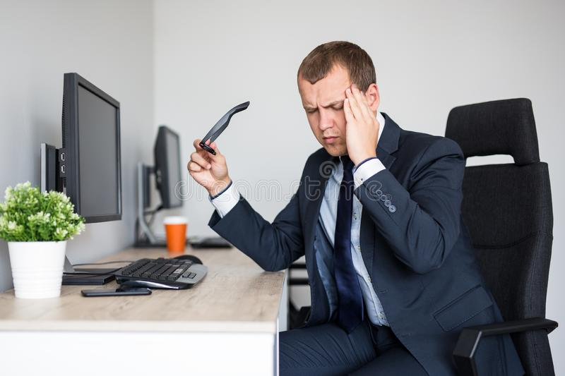 Stressed young business man with headache working in office royalty free stock photo