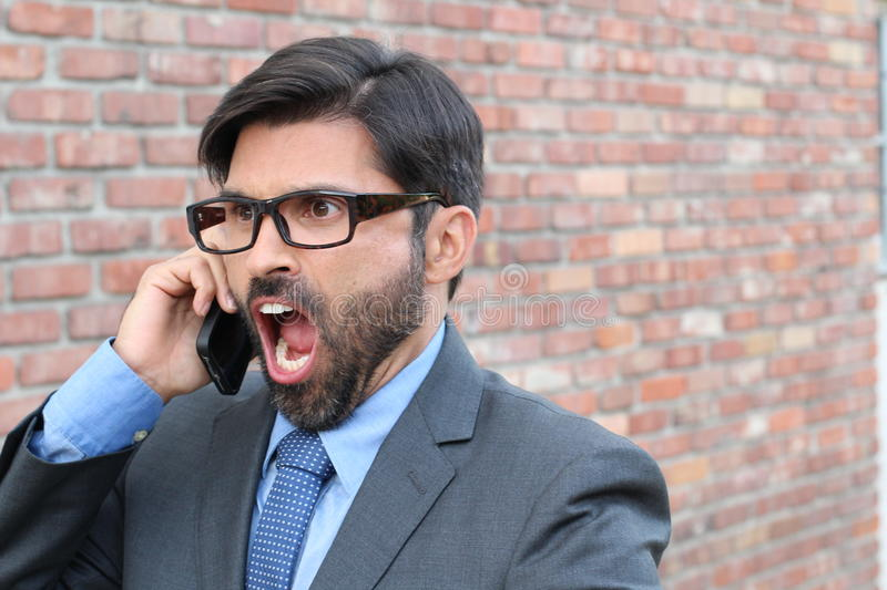 Stressed, young businessman screaming into phone royalty free stock images