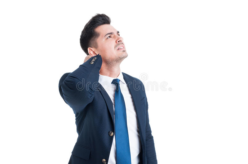 Stressed young businessman suffering from neck or cervical pain royalty free stock photo