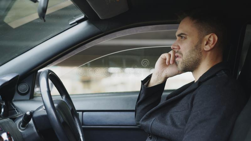 Stressed businessman swearing and talking phone while sitting inside car outdoors stock photos