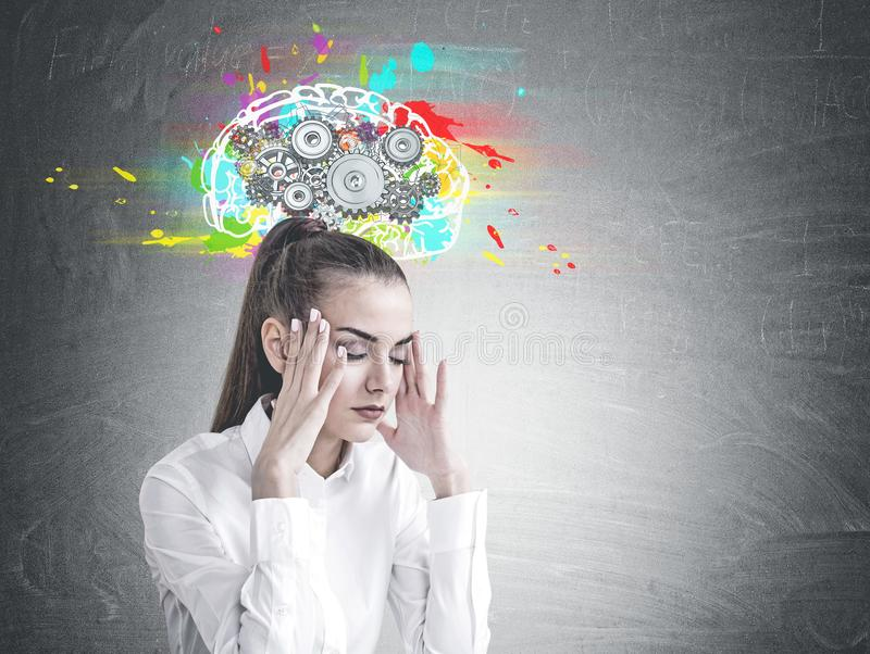 Stressed young businesswoman, cog brain royalty free stock image