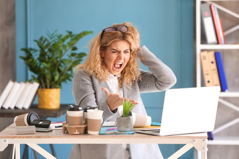 Stressed young businesswoman at table in office stock images