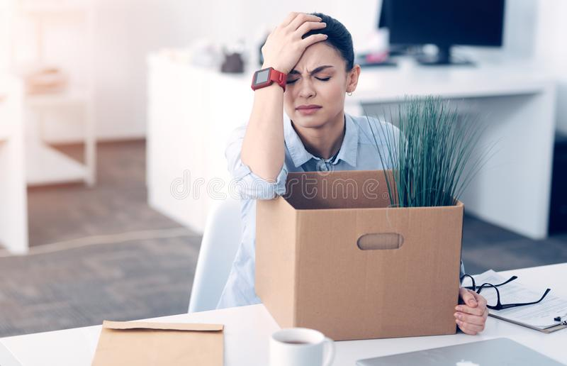 Stressed young lady having nervous breakdown after dismissal. Why did this happen to me. Tired female office worker grimacing and holding her hand on a head royalty free stock image